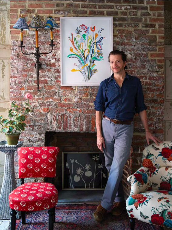 John Derian stands against a brick wall in his new West Village shop on Christopher Street NYC